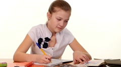 School girl doing her homework and writes essay on white background, slow motion - stock footage