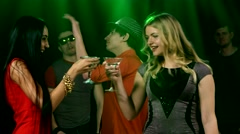 Party dancing. girl in the foreground clink glasses and drink martini Stock Footage