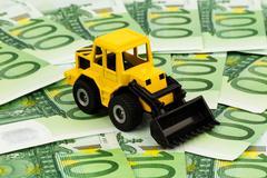 Excavator on euro banknotes Stock Photos