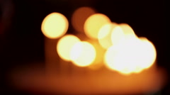 Many lot out focus candles burning flame in church cathedral. Hand put light on Stock Footage