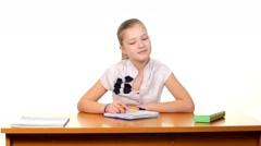 Cute school girl sitting, thinking and writing homework, essay in workbook on Stock Footage