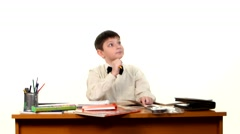 School boy doing his homework thinking about the topic of essay on white - stock footage