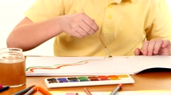 Little boy sitting at the table painting colors on white background Stock Footage