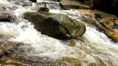 Big boulders in stream. Slipper stones and foamy chilly water around. - stock footage