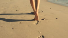 Woman Leaving Footprints in the Sand on the Beach Stock Footage