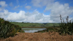 New Zealand Catlins quiet lake in front of spreading hills Stock Footage