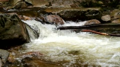 Stream is bended between boulders. Slipper stones and chilly water - stock footage