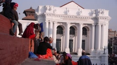 People sittinng on temple stairs with Old Royal Palace,Kathmandu,Nepal Stock Footage