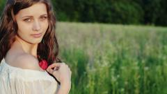 A young girl with bare shoulders in the midst of green fields and poppy in hand Stock Footage