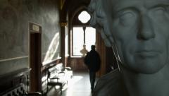 Statue in museum, bust, with paintings and art patron Stock Footage