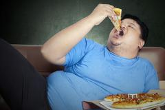 Obese person eats pizza - stock photo