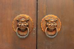 Traditional Chinese old door with lion head knockers - stock photo