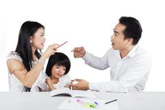 Two parents arguing near to their child - stock photo