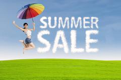 Woman jumps with summer sale sign Stock Photos