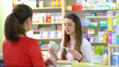 Young female pharmacist holding a receipt and selling medicine in a drugstore Stock Footage