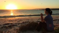 Godly Woman Praying on The Beach at Sunset With Hands Folded - stock footage