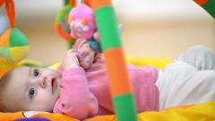 Innocent baby smiling and playing with toys - stock footage