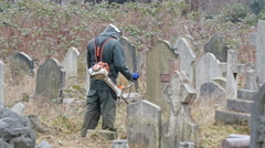 A man mowering the grasses in the cemetery - stock footage