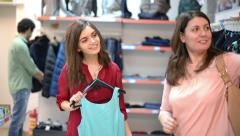 Happy woman showing some clothes in supermarket out of the cloakroom Stock Footage