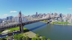Cars ride by Queens Bridge over East River and Roosevelt Island Stock Footage