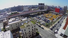 Two trains ride by railroad near car parking at summer Stock Footage