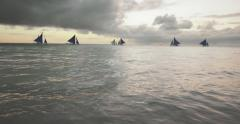 Silhouettes of sailboats sailing on calm water of sea at peaceful morning Stock Footage
