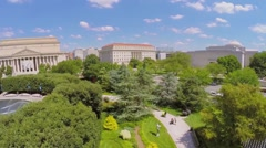 People walk near art objects in garden not far from edifices Stock Footage