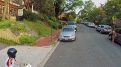 Boy rides by Mt. Pleasant Street NW in residential neighborhood - stock footage