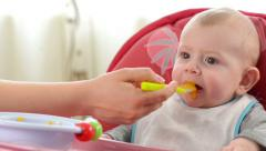 Baby boy eating in a high chair at home Stock Footage