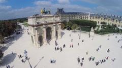 Many people walk near Arc de Triomphe du Carrousel Stock Footage