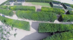Young boy hides in bush maze on square Place du Carrousel Stock Footage