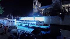 Tourists vessel sails near Cathedral Notre-Dame de Paris Stock Footage