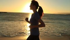 Woman Running at Ocean in Silhoutte Stock Footage