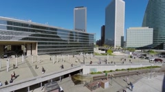 Birds fly in business centre La Defense with many people walk Stock Footage