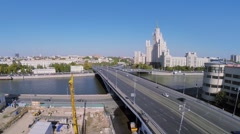 City traffic on Bolshoy Ustyinsky bridge near skyscraper Stock Footage