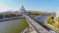 Tourists walk by Patriarshiy bridge near Christ Savior Cathedral Stock Footage