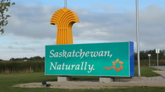 Saskatchewan sign with traffic passing. Manitoba Saskatchewan border. Stock Footage