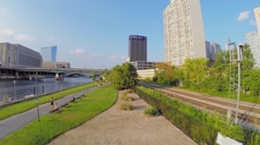 People run by quay of Schuylkill river near railway Stock Footage