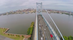 Vehicles drive by Benjamin Franklin Bridge over Delaware river Stock Footage