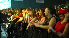 Viewers stand at the fence near the stage at a concert Stock Footage