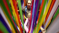 Mother and daughter go through the colored ribbons spreading it Stock Footage