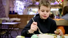 A boy with bread in his hand sits in the cafe at the table Stock Footage