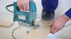 Man cuts the board of flooring using an electric jig saw Stock Footage