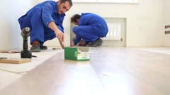 Two workers install flooring in the new apartment - stock footage