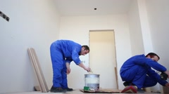 Installation of parquet: one worker drill holes, other smears glue - stock footage