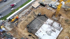 The foundation of building under construction next to road Stock Footage