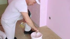 Builder sitting on the floor and mixing plaster in a bucket. Stock Footage