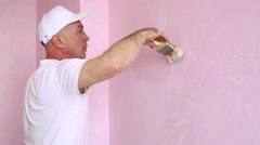 Builder with a brush in hand painting walls at the pink room. Stock Footage
