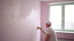 Builder in white cap is painting wall at the light pink room. Stock Footage