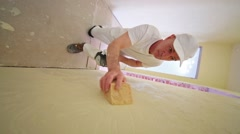 Worker in white cap is polishing yellow plaster wall. Stock Footage